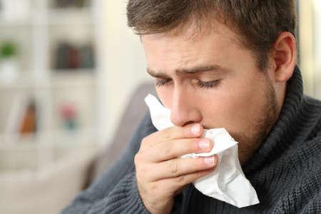 Hombre tosiendo cubriendo la boca con un pañuelo de papel sentado en un sofá en el interior de una casa