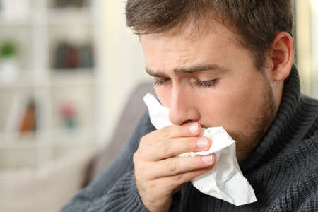 Man coughing covering mouth with a tissue sitting on a couch in a house interior