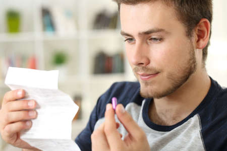 Man reading a leaflet before to take a pink pill sitting on a sofa in the living room in a house interior