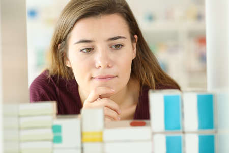 Front view of a doubtful customer choosing medicines in a pharmacy
