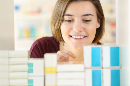 Front view portrait of a customer searching medicines in a pharmacy interior