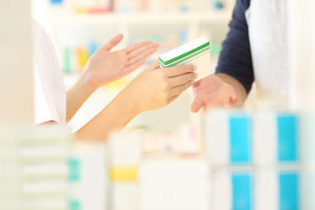 Close up of a pharmacist hands selling medicine to a customer in a pharmacy interior