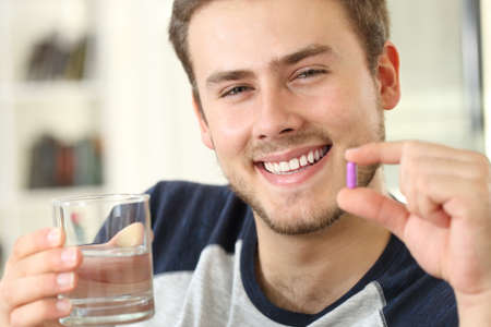 Happy man holding a pink pill and a glass of water looking at camera sitting on a sofa in a house interior
