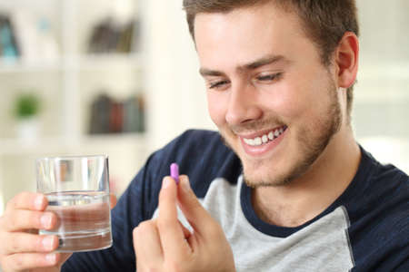 Happy man ready to take a capsule sitting on a sofa in the living room in a house interior