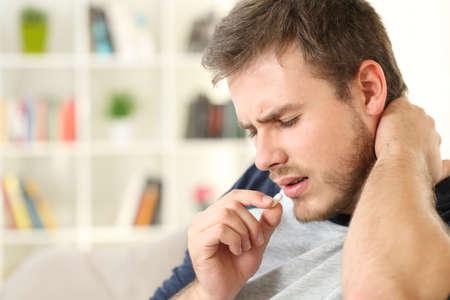 家のインテリアのリビングルームのソファに座って錠剤を服用して不平を言う負傷した男性