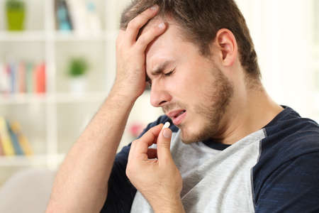 Man suffering headache taking a pill sitting on a sofa in the living room in a house interior