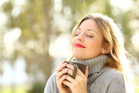 Porträt eines entspannten tragenden Trikots des Mädchens, das einen Tasse Kaffee hält und draußen in einem Park im Winter atmet