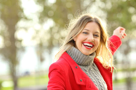 Portrait of a joyful beauty woman with perfect smile dancing carefree outdoors in a park in winter with copy space at side Stock Photo