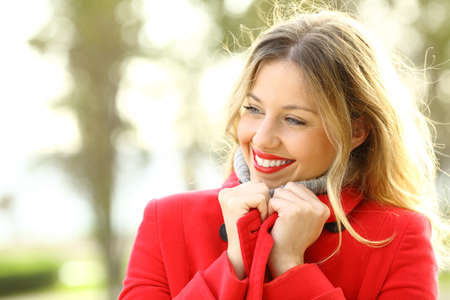 self care: Portrait of a beauty woman warmly clothed wearing a red jacket in winter in a park with copy space
