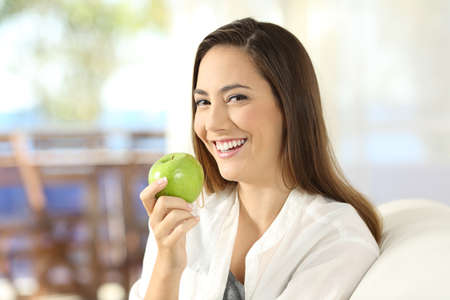 Portrait of a happy woman holding a healthy green apple sitting on a sofa in the living room at home
