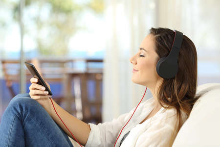 Side view portrait of a woman relaxing listening to music in a smart phone wearing headphones sitting on a sofa in the living room at home