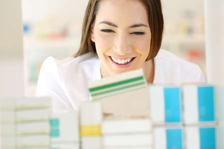 Front view portrait of a happy pharmacist finding medicine in a pharmacy shelf