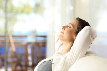 Seitenansichtporträt eines entspannenden Sitzens der glücklichen Frau auf einer Couch auf Ferien in einer Wohnung auf dem Strand