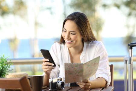 Front view portrait of a tourist searching information on line in a smart phone and a map on vacations in an hotel terrace