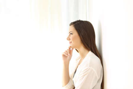 Side view portrait of a woman thinking leaning on a wall at home isolated on white at side