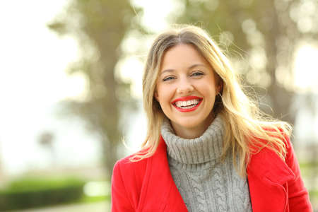 Portrait of a happy woman laughing wearing red jacket and looking at camera in winter