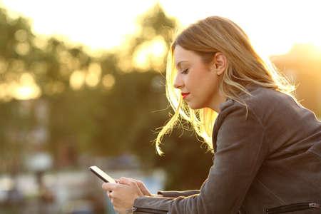 Retrato de vista lateral de una mujer seria leyendo texto en un teléfono inteligente en un balcón de la casa al atardecer