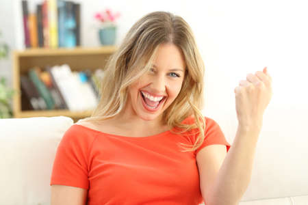 Front view portrait of an excited successful woman looking at camera sitting on a couch in the living room at home Stock Photo