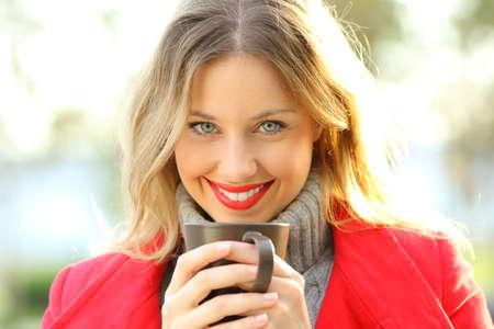 Retrato de vista frontal de una cara de mujer feliz mirando a usted sosteniendo una taza de café con una chaqueta roja en invierno Foto de archivo - 89607936