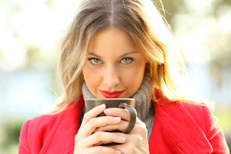 bebes niñas: Front view portrait of a sensual woman with blue eyes looking at camera holding a coffee cup outdoors in a park