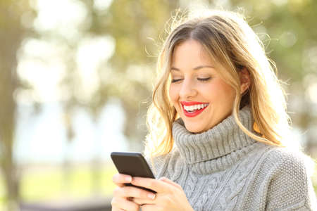 hands free phone: Portrait of a happy woman wearing sweater reading text on a mobile phone outside in winter