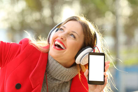 Garota feliz vestindo jaqueta vermelha e fones de ouvido, ouvindo música e mostrando a tela do smartphone em um parque no inverno