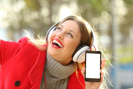 Szczęśliwa dziewczyna jest ubranym czerwoną kurtkę, hełmofony słucha muzyka i pokazuje smartphone ekran w parku w zimie