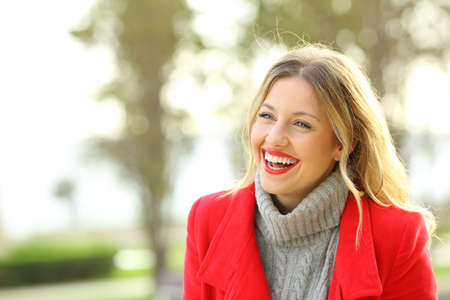 Funny woman wearing a red jacket laughing outside in a park in winter