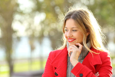 Happy pensive lady wearing a red jacket looking at side in a park in winter
