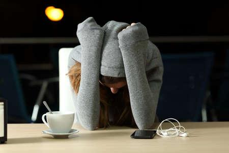 Ritratto di vista frontale di un adolescente triste lamentarsi in un bar nella notte