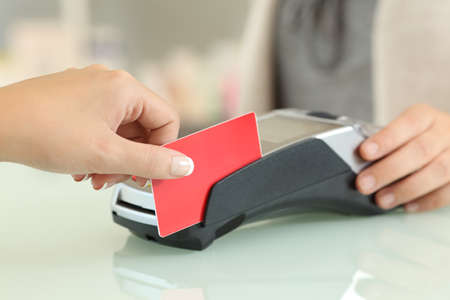 Close up of a customer hand passing credit card through the reader on a counter in a shop