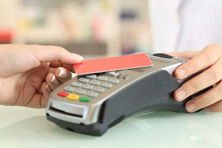 Close up of a woman hand paying with a contact less credit card in a shop counter