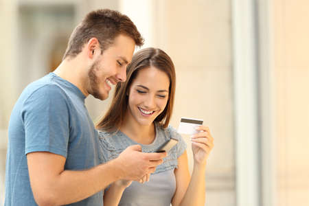 Happy couple paying on line with credirt card and smart phone on the street Stockfoto
