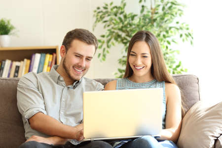 Front view portrait of a young happy couple using a laptop together sitting on a sofa in the living room at home Foto de archivo