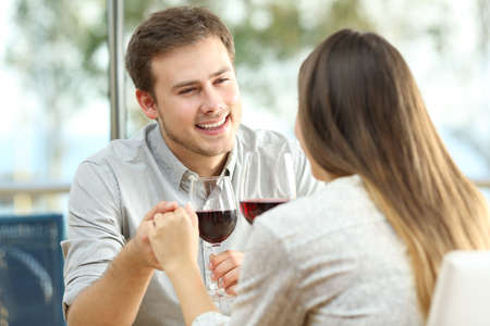 Successful date of a couple drinking wine in a restaurant