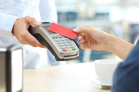 Schließen Sie oben von einer Kundenhand, die mit einem kontaktlosen Kreditkartenleser in einer Bar zahlt