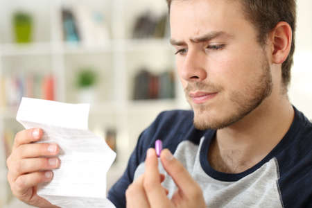 Suspicious man reading the leaflet of a pill sitting on a couch at home