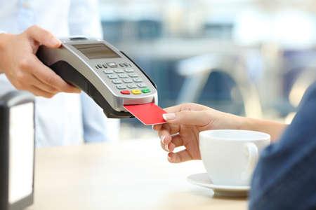 Sluit omhoog van een klantenvrouw die met creditcardlezer betalen in een bar Stockfoto