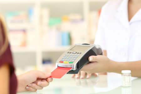 Close up of a pharmacist hands charging with credit card reader on a counter in a pharmacy