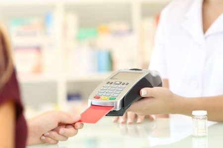 Sluit omhoog van een apothekerhanden belastend met creditcardlezer op een teller in een apotheek Stockfoto