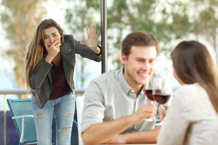Cheater betrapt door zijn trieste vriendin daterend met een ander meisje in een coffeeshop Stockfoto