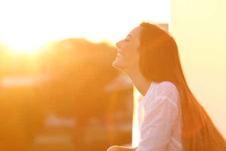 Zijaanzichtportret van een gelukkige vrouw die diepe verse lucht ademen bij zonsondergang in een huisbalkon Stockfoto