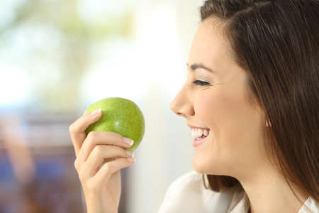 Side view portrait of a happy woman holding an apple ready to eat at home