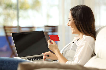 Happy woman paying on line with a credit card and a laptop sitting on a sofa in the living room in a house interior
