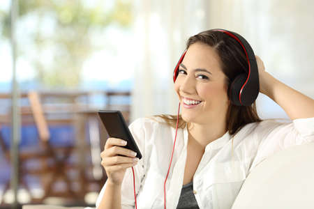 Happy woman listening to music wearing headphones looking at camera sitting on a sofa in the living room of a house interior Stock Photo