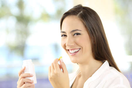 Portrait of a happy woman holding a vitamins pill and bottle Archivio Fotografico