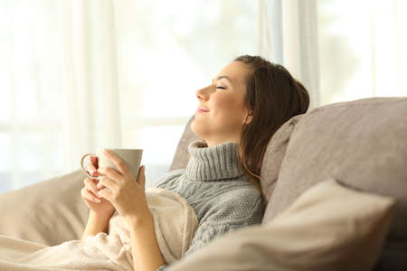 Woman relaxing holding a coffee mug sitting on a sofa in the living room in a house interior Banque d'images