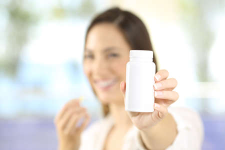 Close up of a woman showing a bottle of pills