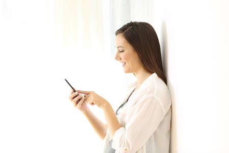 Zijaanzichtportret van een gelukkige vrouw die online inhoud in een slimme telefoon selecteren die aan wit aan kant wordt geïsoleerd