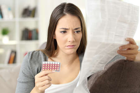 Worried woman reading contraceptive pills leaflet sitting on a couch at home